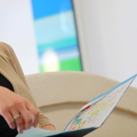 Eine Frau hält eine Broschüre ein der Hand