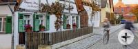 Ein kleines Fachwerkhaus mit grünen Fensterläden und Holzzaun, vorne eine Radfahrerin auf Kopfsteinpflaster