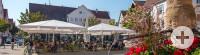 Marktplatz Metzingen, vorne ein mit roten Blumen geschmückter Brunnen, links Menschen sitzen in einer Gartenwirtschaft