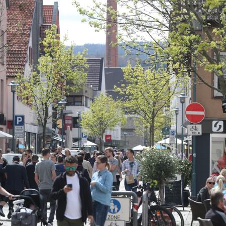 Viele Menschen auf einer Straße beim Einkaufen in der Innenstadt, links und rechts Häuser