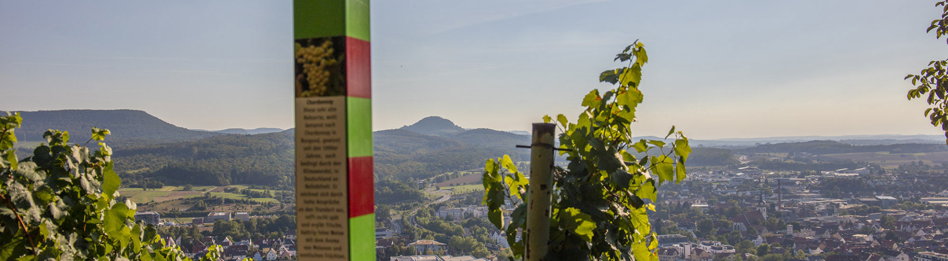 Red and green striped information board on the wine adventure trail with a view of Metzingen and the Swabian Alb