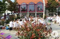 Menschen sitzen in weißer Kleidung auf Bänken vor dem Rathaus