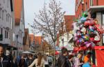 Menschen bummeln durch eine Einkaufsstraße, recht viele bunte Luftballons