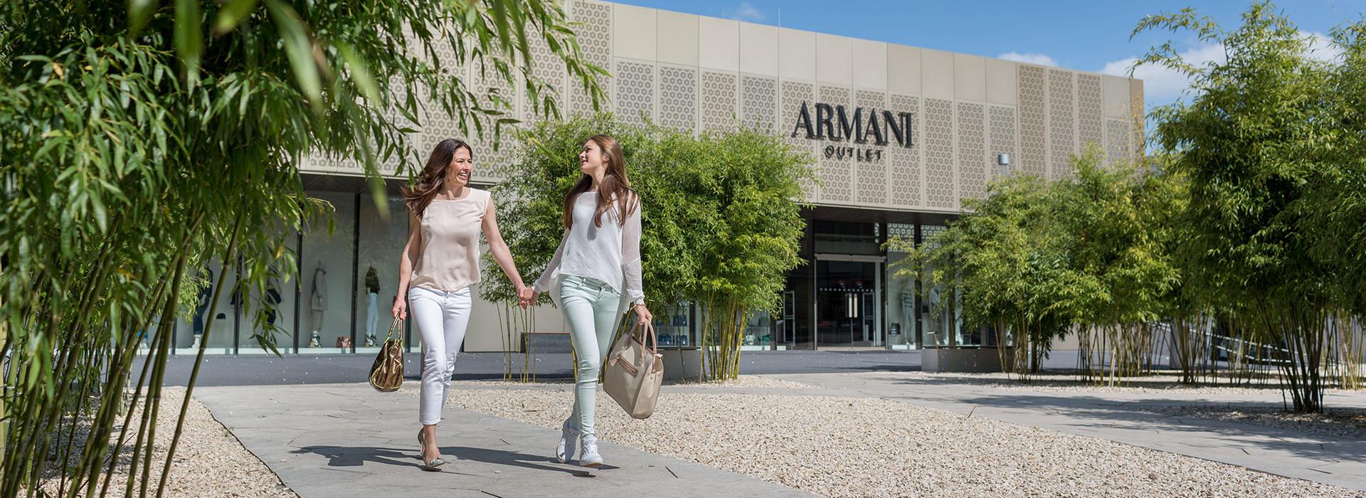 Zwei Frauen bummeln mit Einkaufstaschen im Fabrikverkauf, links und rechts Bäume
