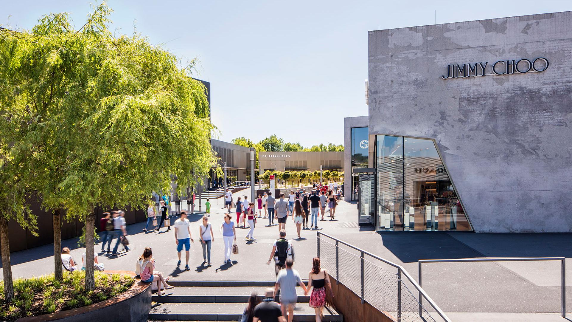 Auf einer Treppe und einer Straße sind viel Menschen mit Einkaufstüten, links steht ein großer Baum, rechts ein Fabrikverkaufsgebäude