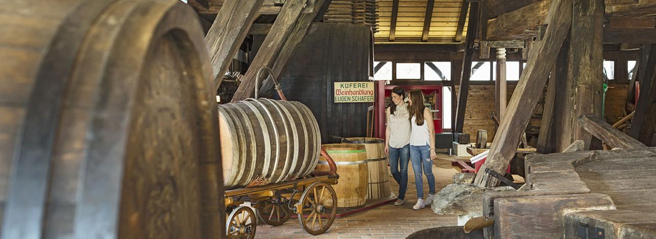 Zwei Frauen betrachten ein großes Weinfaß im Weinbaumuseum