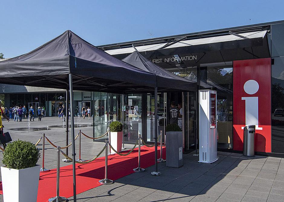 TouristInformation Metzingen, vor dem Eingang ein ausgerollter roter Teppich und Sonnenschirm