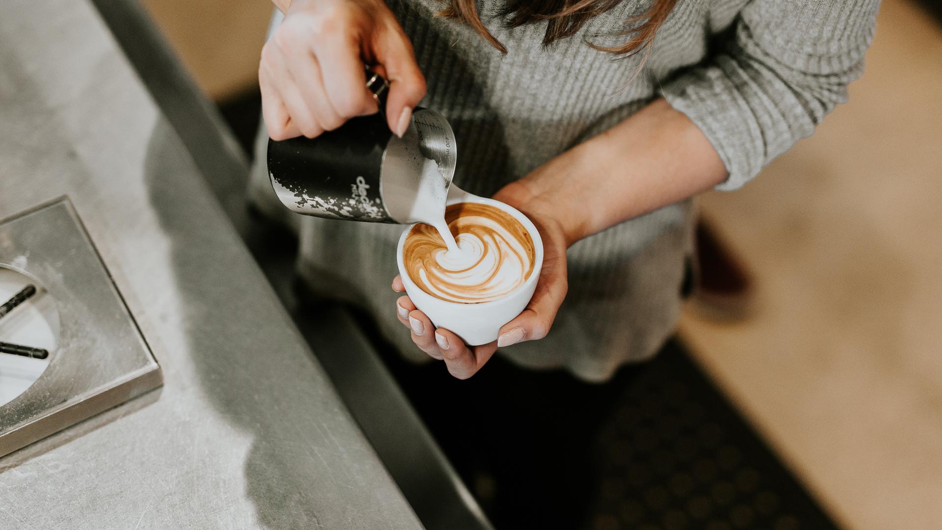 Eine Tasse Kaffe, in die mit einem Kännchen Milch eingeschenkt wird