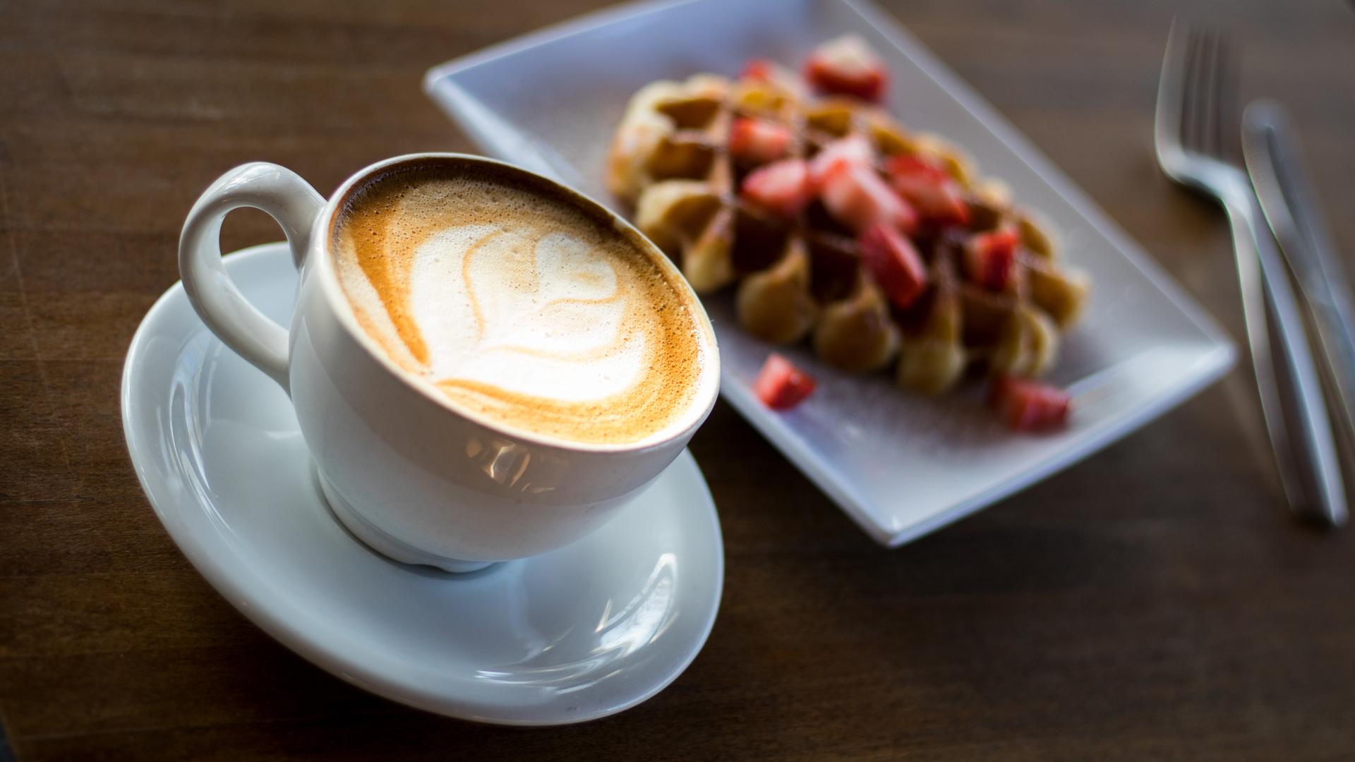 Eine Tasse Cappuccino und Waffel auf einem Teller