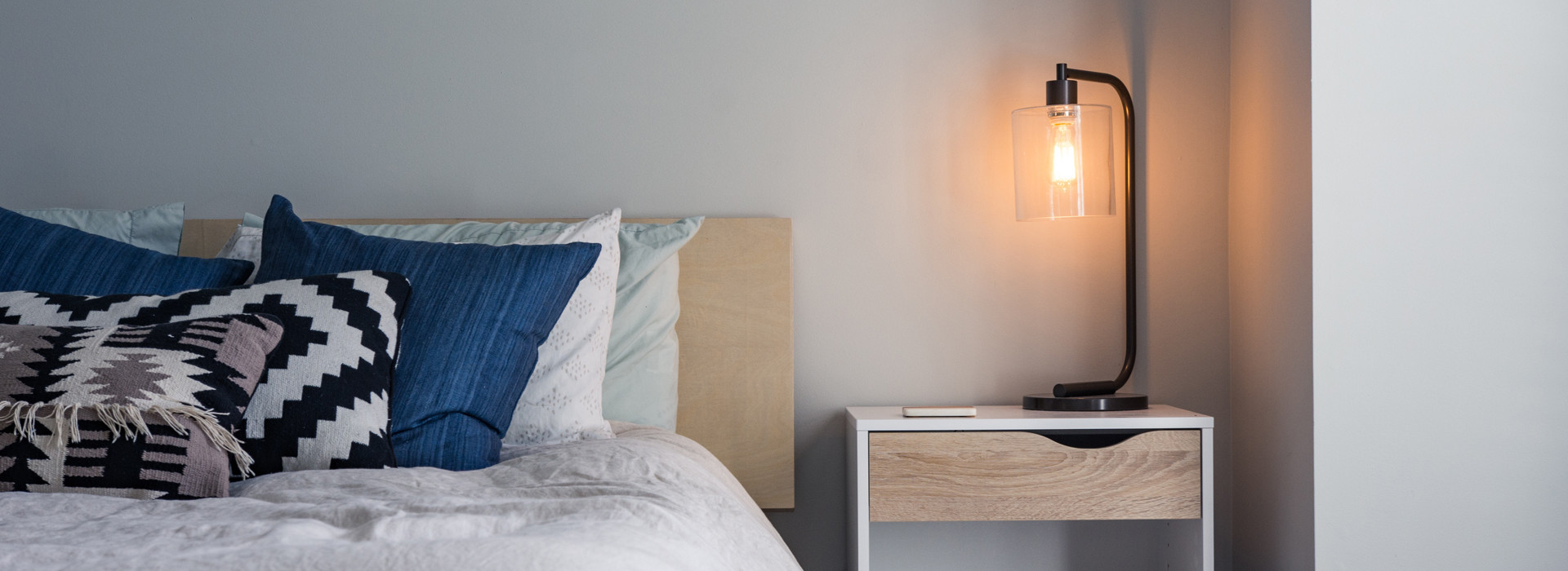blaue Kissen liegen auf einem Bett im Hotelzimmer, rechts brennt ein eine Nachttischlampe