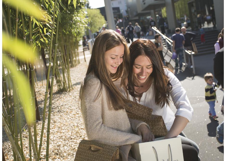 Zwei Frauen sitzen auf einer Mauer mit vielen Einkaufstüten