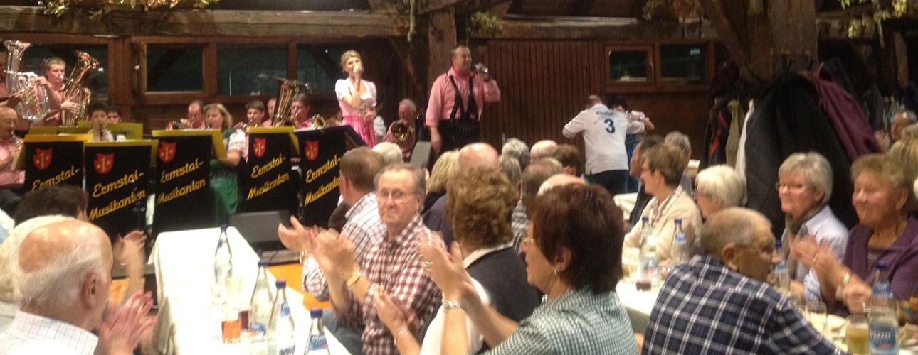 Menschen feiern in der Kelter, im Hintgergrund singt ein Paar