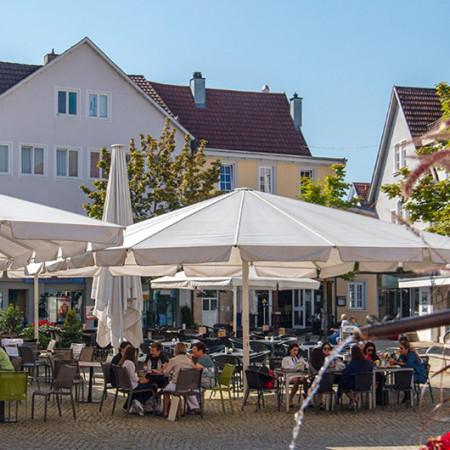 Menschen sitzen in einer Gartenwirtschaft auf dem Marktplatz Metzingen, darüber sind weiße Sonnenschirme gespannt