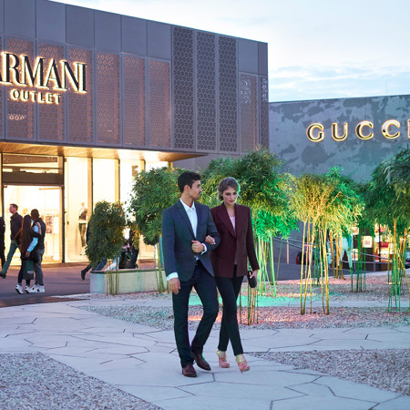 Paar geht in der beleuchteten Outletcity Metzingen einkaufen