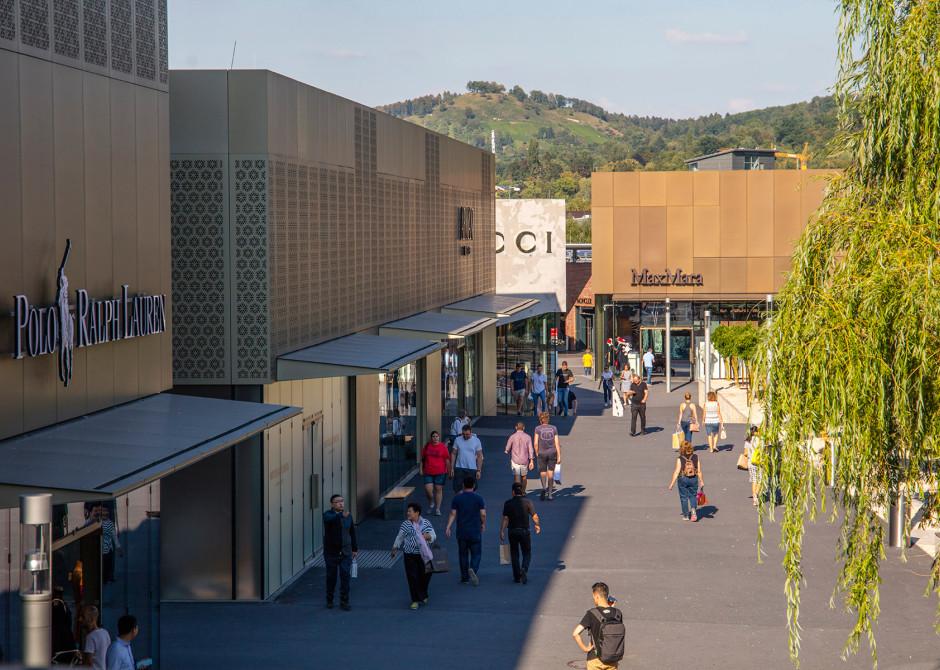 Menschen mit Einkaufstüten, rechts ein großer Weidenbaum, links Einkaufsgeschäfte