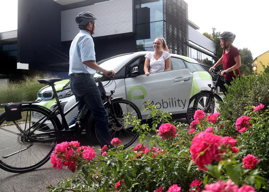 Fahrradfahrer und ein Auto mit elektrischem Betrieb