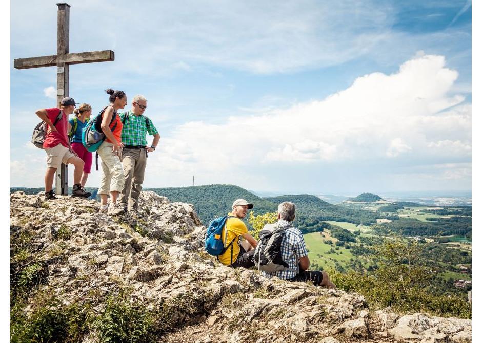 Eine Menschengruppe blickt von einem Gipfelkreuz ins Tal