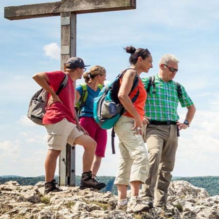 Vier Wanderer stehen auf einem Gipfel und schauen nach unten in das Tal