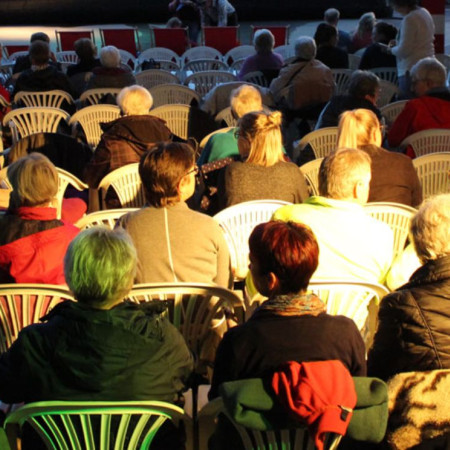 Viele Besucher sitzen in der Dämmerung im Open Air Kino