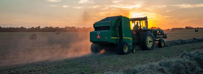 Traktor und Ballen-Presse auf dem Feld