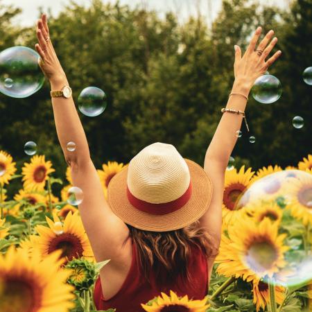 Frau mit Hut im Sonnenblumenfeld